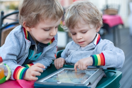 Two little boys having fun with tablet pc, outdoors photo