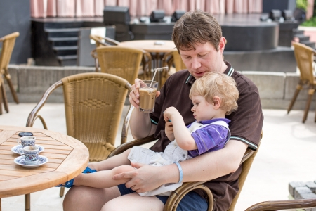 Young man and his little son sitting at the table in summer restaurant Stock Photo - 20379137