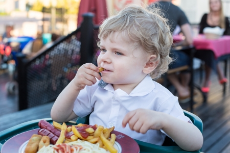 Lovely little boy eating french fries in summer, outdoors