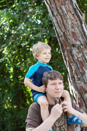 Young father giving little boy a ride on shoulders photo