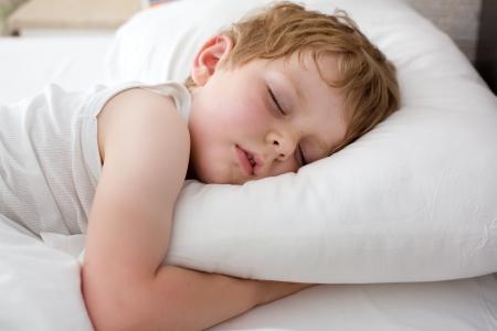Malý blond chlapec spí v posteli Reklamní fotografie