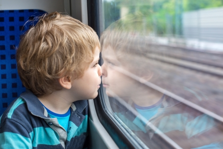 Sweet toddler boy looking out train window outside, while it moving. travel Stock Photo