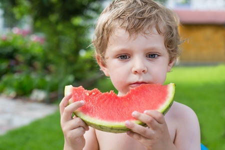 Adorable little toddler boy with blond hairs eating watermelon in summergarden Stock Photo - 20644905