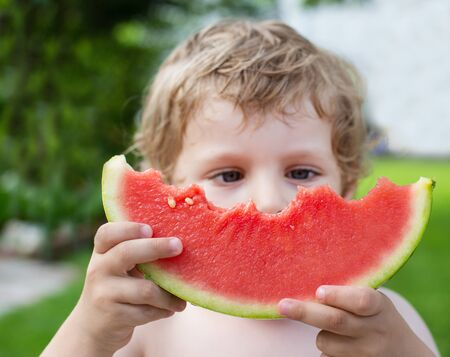 munch: Adorable little toddler boy with blond hairs eating watermelon in summergarden. Selective focus on watermelon Stock Photo