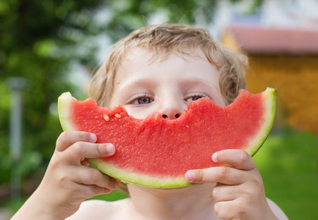 Adorable little toddler boy with blond hairs eating watermelon in summergarden. Selective focus on watermelon Stock Photo