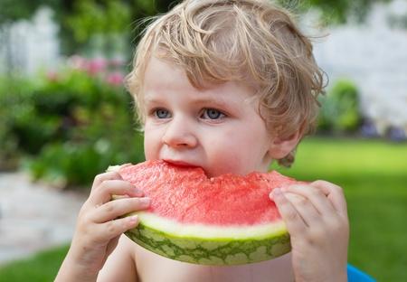 summergarden: Adorable little toddler boy with blond hairs eating watermelon in summergarden