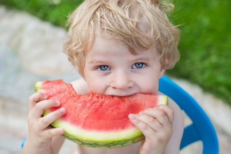 Adorable little toddler boy with blond hairs eating watermelon in summergarden Stock Photo - 20644912