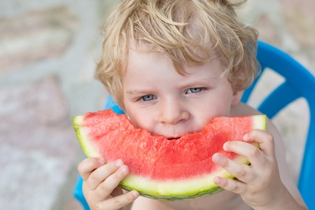 Adorable little toddler boy with blond hairs eating watermelon in summergarden Stock Photo - 20644903