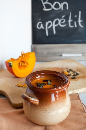 Pumpkin vegetable cream soup in brown bowl with piece pumpkin on cutting board photo