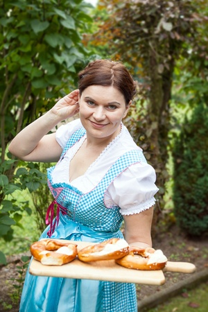 dirndl dress: Happy beautiful girl in dirndl dress holding Oktoberfest pretzel in hands Stock Photo