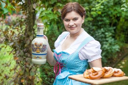 dirndl dress: Young beautiful girl in dirndl dress holding Oktoberfest pretzel and beer mug in hands Stock Photo