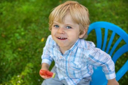summergarden: Cute little toddler boy with blond hairs eating watermelon in summergarden