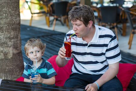 Father and little son sitting in cafe with cocktail on sunny summer day and drinking photo