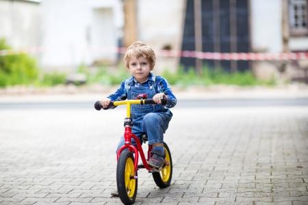 Malý batole chlapec se učí jezdit na svém prvním kole