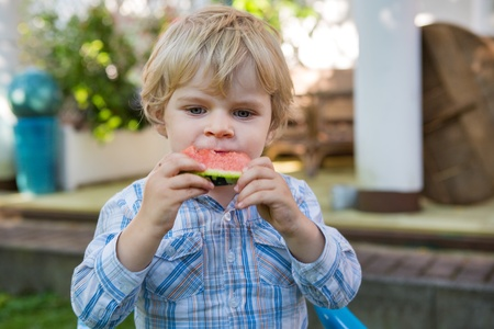 Adorable little toddler boy with blond hairs eating watermelon in summergarden