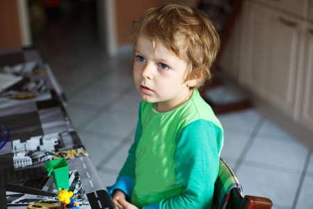 Little boy watching tv in homes kitchen, indoor. photo