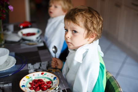 Two little brother boys having oat mash and berries for breakfast photo