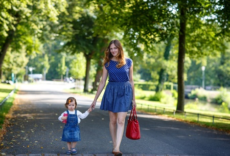 Beautiful mother and little daughter walking in summer park photo