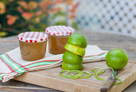 Homemade lemon and lime jam in a glass jar and fresh fruits photo