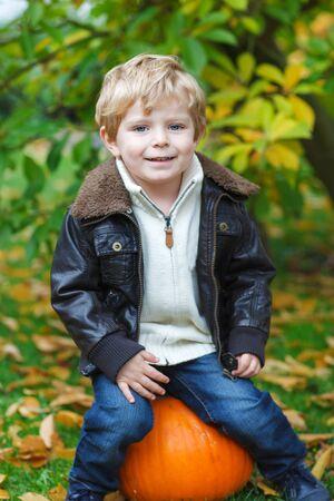 Little toddler boy sitting on big orange pumpkin in autumn garden photo