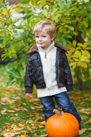 Little toddler boy having fun with big orange pumpkin in autumn garden photo