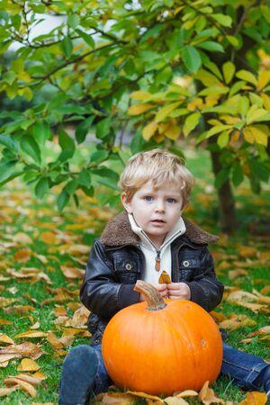 Little toddler boy having fun with green pumplkin photo