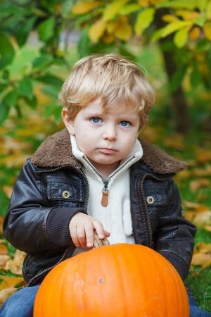 Little toddler boy with big orange pumpkin in autumn garden photo