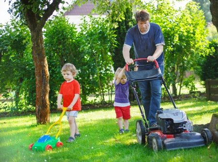 lawn mower: Man and two little sibling boys having fun with lawn mower in garden Stock Photo