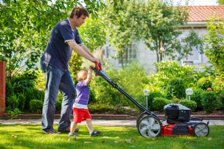 Man and his little son having fun with lawn mower in summer garden photo