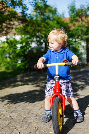 Little toddler boy riding on his bycicle in summer garden photo