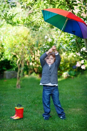 Little cute toddler boy with colorful umbrella and boots in a park photo