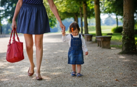 Little cute baby girl walking with beautiful mother in summer park Stock Photo