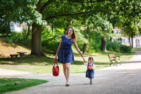 Beautiful mother and little daughter walking together in summer park photo