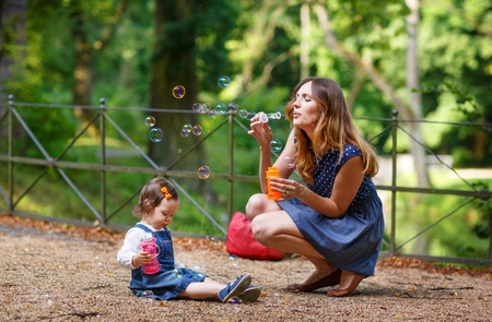 Beautiful mother and little daughter blowing soap bubbles together in summer park photo