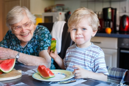 great grandmother: Little toddler boy and his great grandmother eating watermelon in home kitchen. Selective focus on child