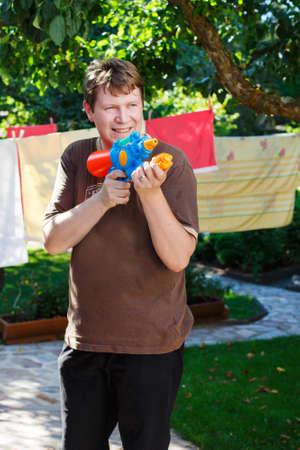 water gun: Young man having fun with water gun in summer garden