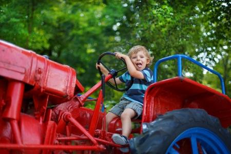 Portret van de kleine blonde jongen in de tractor in de zomer, buiten