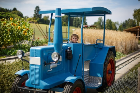 Portrait of little blond boy in tractor in summer, outdoors photo