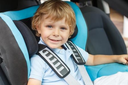 car seat: Portrait of little boy sitting in safety car seat