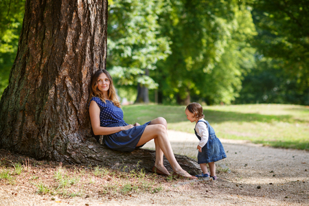 Beautiful mother and little daughter having fun together in summer park photo