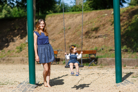 Beautiful mother and little daughter having fun together on playground photo