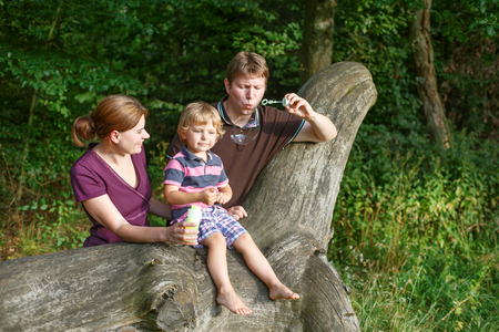 Family of three blowing soap bubbles together in summer forest. Father, mother and little son having fun. photo