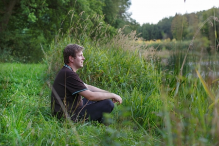 Young handsome man sitting near forest lake, relaxing and meditating in summer evening