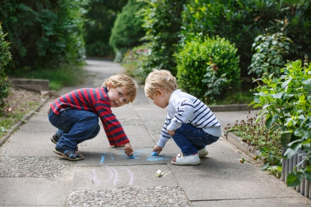 school playground: Two little sibling boys painting with chalk outdoors in summer