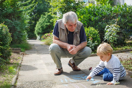 Little blond toddler boy and happy grandfather painting with chalk outdoors in summer photo