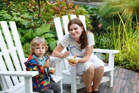 Young woman and little toddler boy eating ice cream, outdoors photo