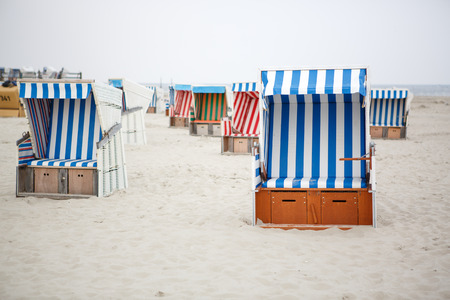 meer: Colorful beach chairs with stripes at the beach of St.Peter Ording, Germany