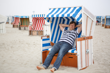 Young happy man sitting in beach chair on the beach of St.Peter Ording, North Sea, Germany photo