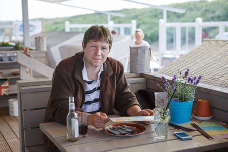 Young happy beautiful man in summer outdoor restaurant photo