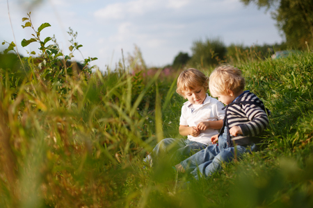 Two little brother boys playing near forest lake on summer evening. Selective focus on boy photo